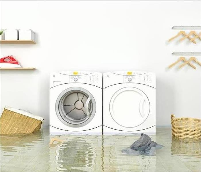 White washer and dryer in a laundry room that are submerged in water